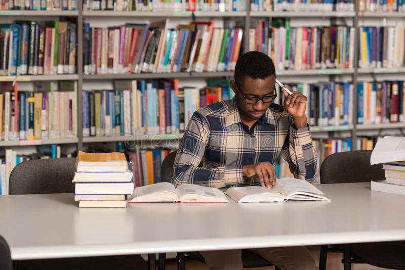 Superior Portrait Of African Clever Student With Open Book Reading It In College  Library   Shallow Depth Of Field