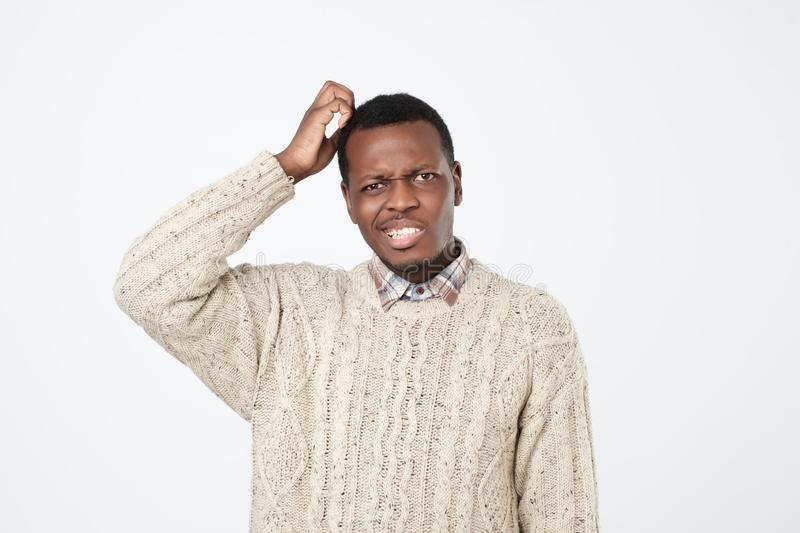 african man in sweater thinking scratching head on white background. How is it supposed to be done concept stock photo