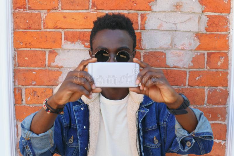 African man taking selfie by smartphone holding hands closeup on brick wall stock images