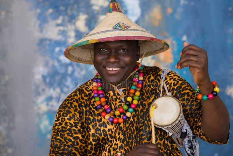 African man in traditional clothes and fulani hat playing on talking drum royalty free stock photography