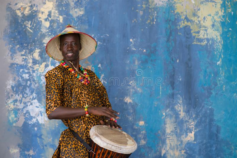 African man in traditional clothes playing djembe drum royalty free stock photos