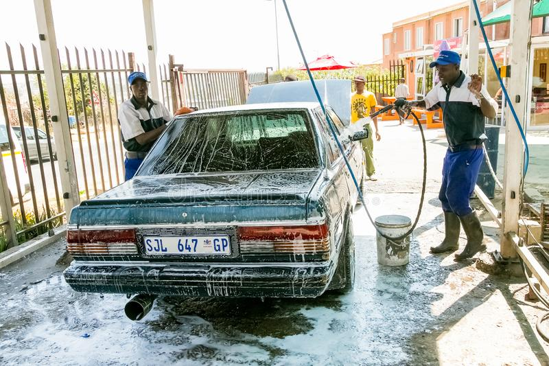 African Man washing a car at a suburban township carwash depot. Johannesburg, South Africa - August 29 2013: African Man washing a car at a suburban township stock photography