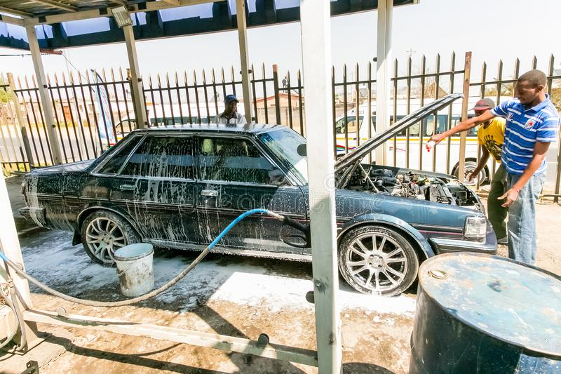 African Man washing a car at a suburban township carwash depot. Johannesburg, South Africa - August 29 2013: African Man washing a car at a suburban township royalty free stock image