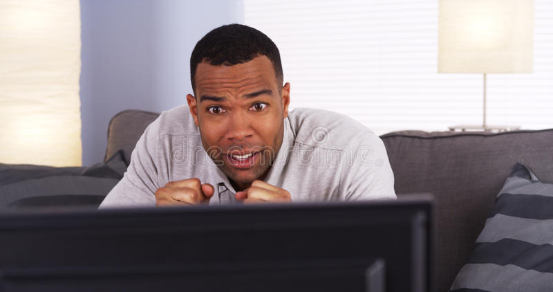 African man watching the game on TV royalty free stock photo