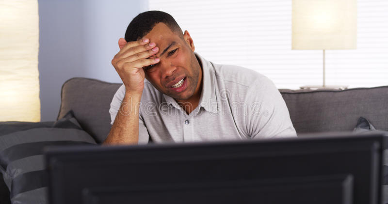 African man watching show on TV. Black man watching show on TV stock photo