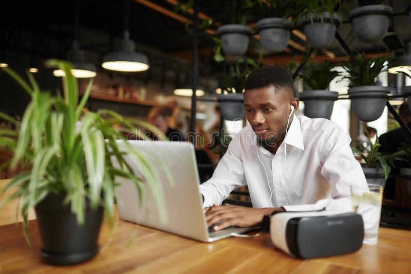 African man typing at laptop, resting in cafe. royalty free stock photography