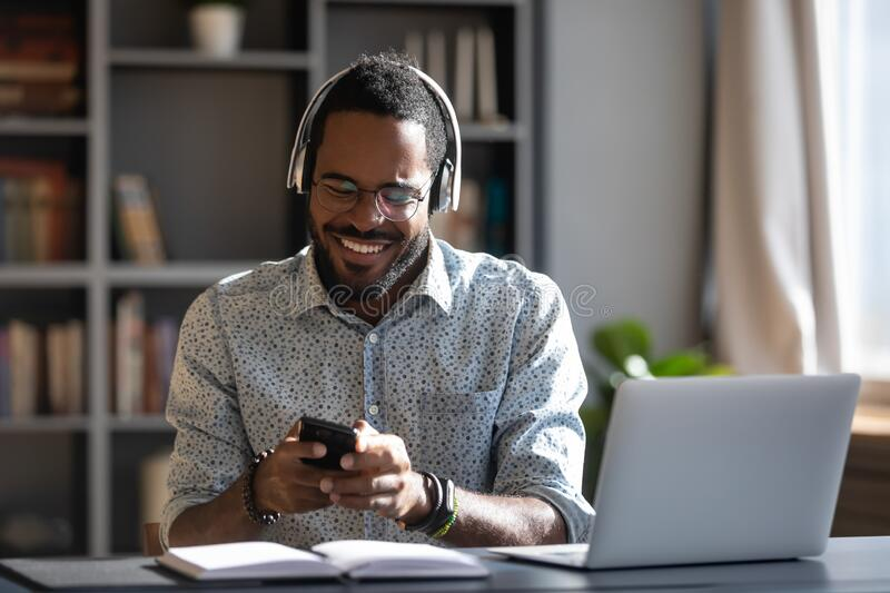 African man holding smartphone wear headphones hearing voice message. African man worker or student sit at desk distracted from study or work hold smartphone stock image