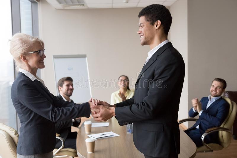 African manager holding hand of successful caucasian worker express respect. African executive manager holding hand of successful caucasian worker express royalty free stock photo