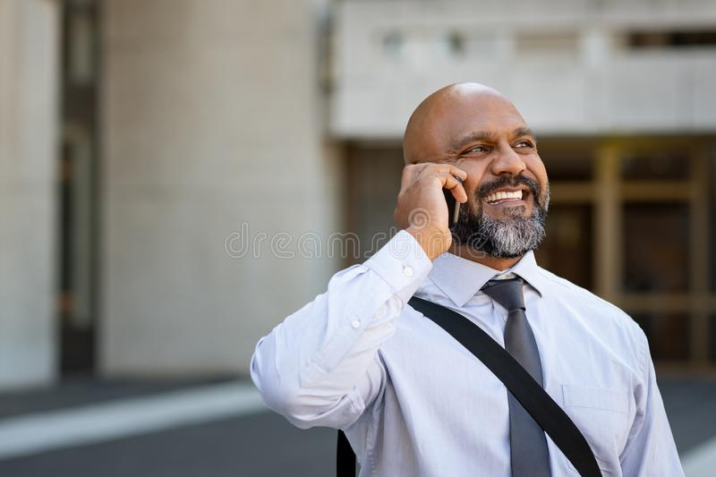 African mature businessman talking on phone outdoor stock photography