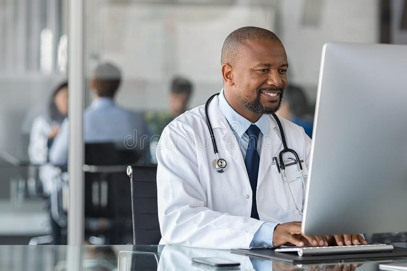 African mature doctor working on computer royalty free stock photos