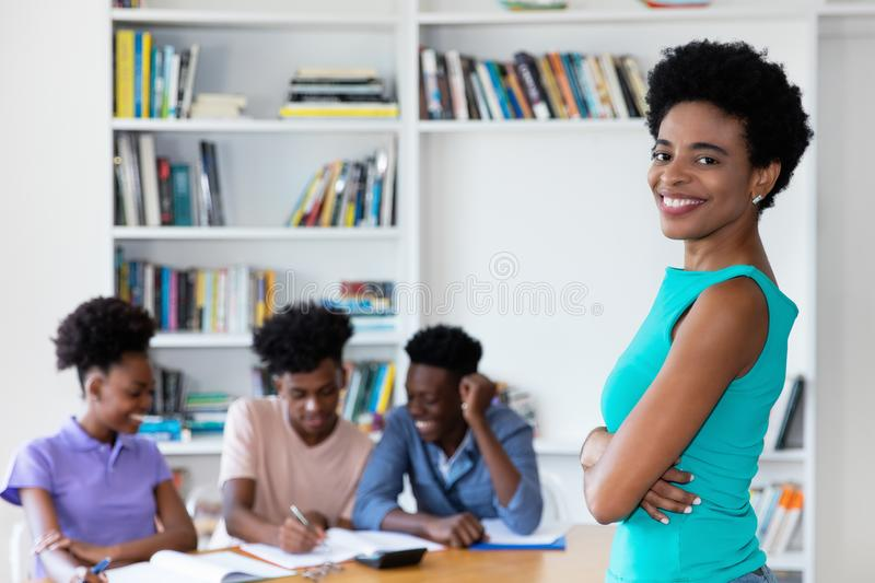 African mature teacher with students at work royalty free stock photography
