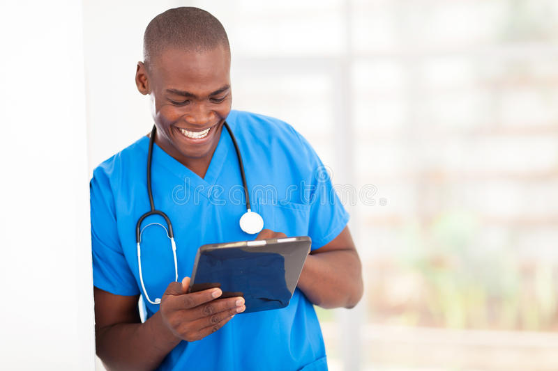 African medical worker tablet computer. Young handsome african american medical worker using tablet computer in hospital royalty free stock photography