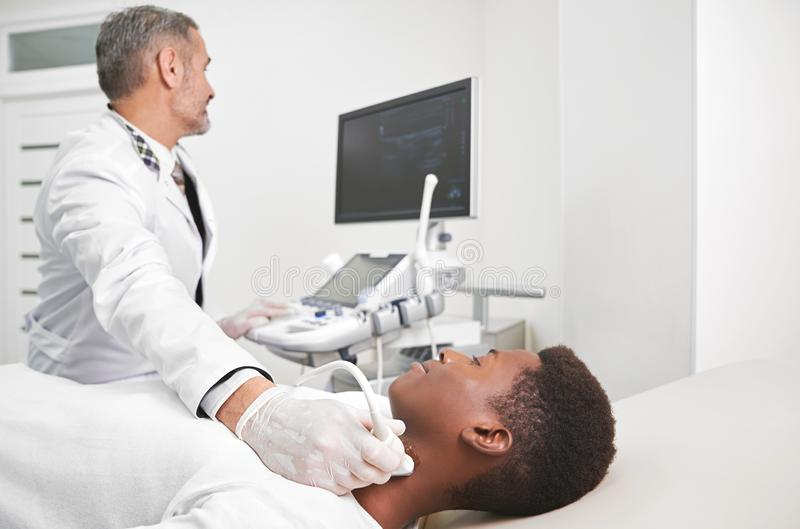 Doctor doing ultrasound diagnosis of lymph node. African men lying in medical cabinet. Sonography, ultrasound diagnostics of lymph nodes on neck. Doctor wearing stock photo