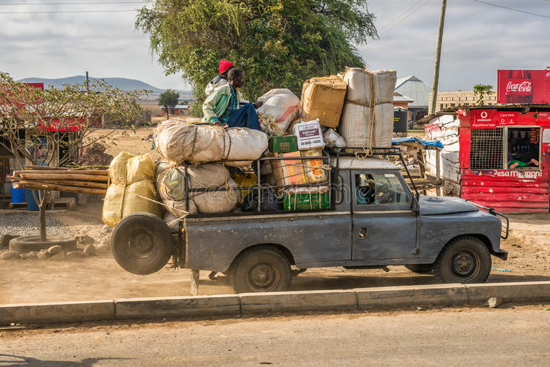 African men transporting goods in an old car. ARUSHA, TANZANIA - OCTOBER 21, 2014 : African men transporting goods in an old car stock images