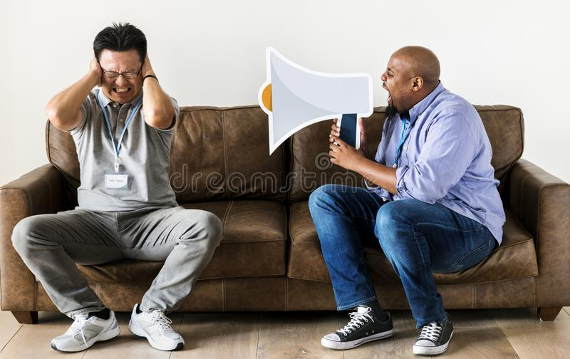 African man using speaker icon and disturbing another man stock image