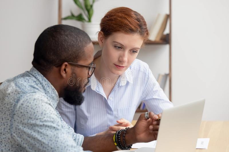 African mentor consultant explaining computer work to caucasian intern client. African american mentor salesman broker consultant explaining computer work to royalty free stock image