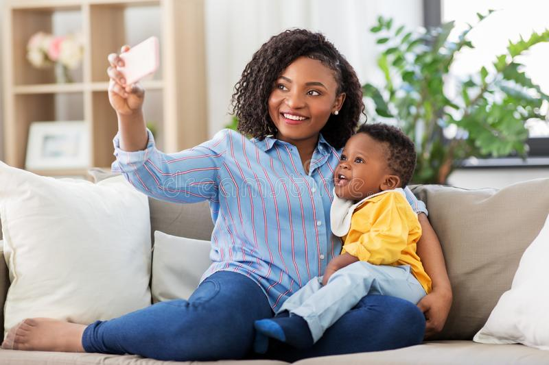 African mother with baby son taking selfie at home. Family, technology and motherhood concept - happy smiling young african american mother with little baby son stock image