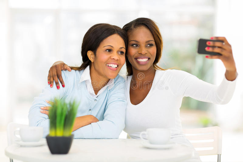 African mother daughter self portrait. Happy middle aged african mother and daughter taking self portrait with smart phone stock photos