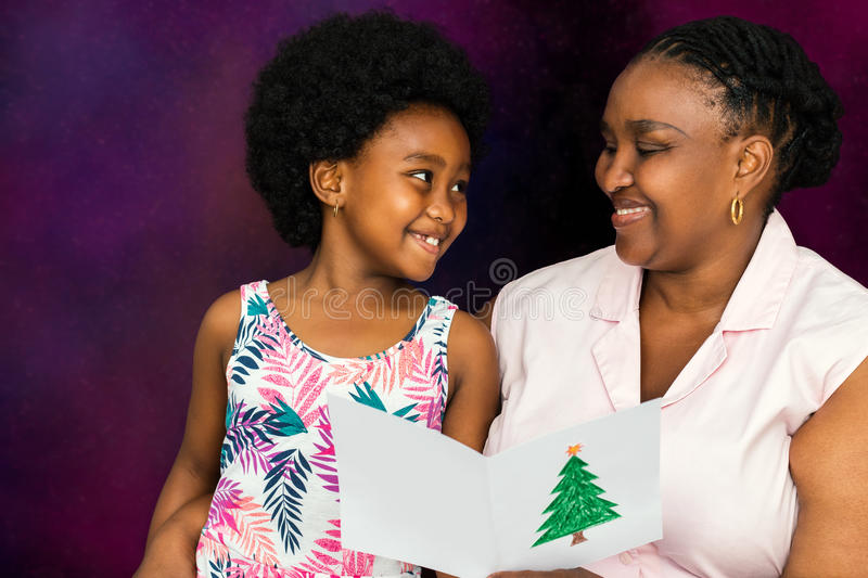 African mother reading christmas card to little girl. royalty free stock image