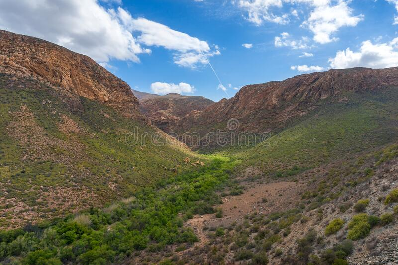 African mountain landscape with green mountain valley and dry arid mountains. Drought and climate change landscape stock photo