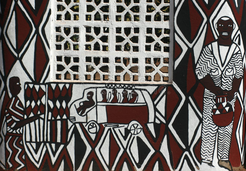 African mud wall with contemporary painting, Ghana. Traditional African mud wall painting is updated with a contemporary design, Ghana stock photo