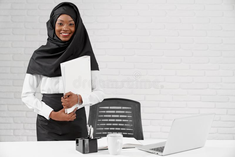 African muslim woman standing at table, holding folder. stock photography