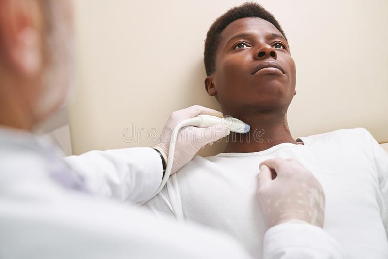 African man on ultrasound diagnosis of lymph nodes on neck. African patient lying, looking up. Doctor doing ultrasound diagnosis, using, holding special device royalty free stock image