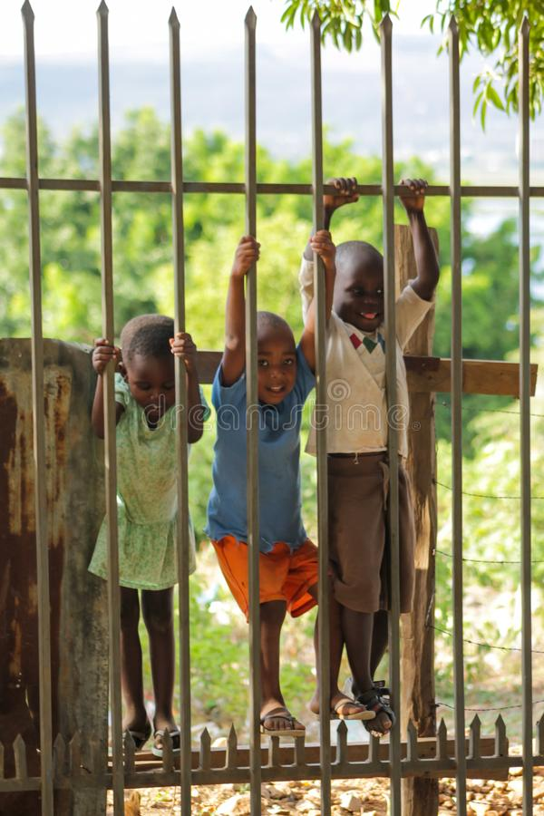 African poor children on the street near fence. African small poor children boys and girls on the street. Slum african people village life royalty free stock images