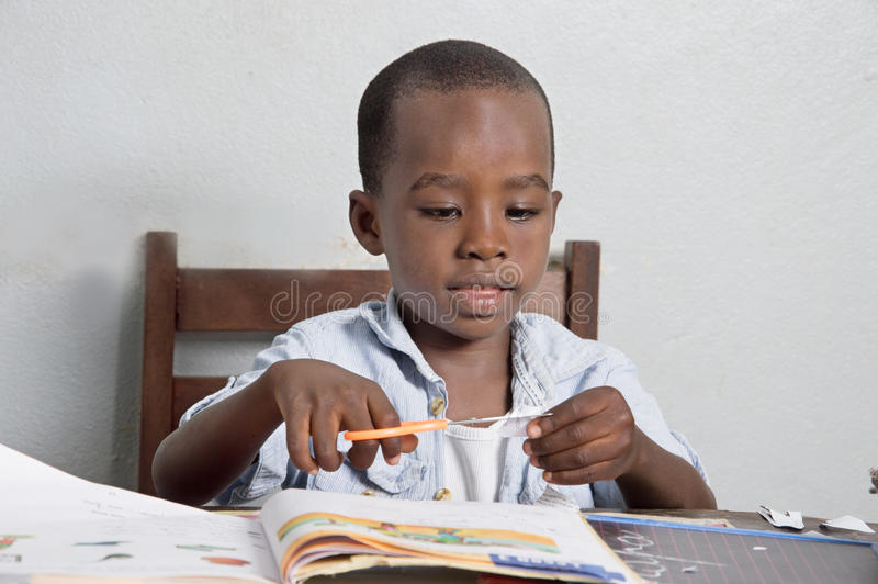 African primary student. Schoolboy cutting a sheet with a chisel on his study table royalty free stock photos