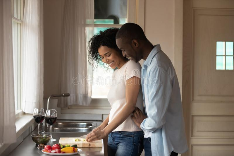 African romantic couple cooking together dinner in the kitchen. 30s african couple talking stand in kitchen at modern home two glasses red wine on countertop stock images