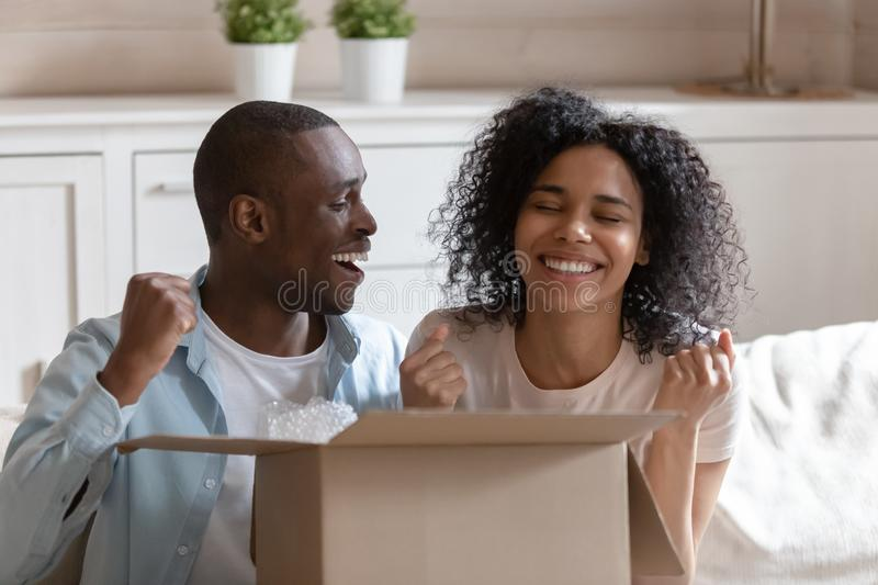 African spouses sit on couch with cardboard box feels happy. African 30s spouses sitting on sofa opening cardboard box feels excited and happy clients receiving stock photography