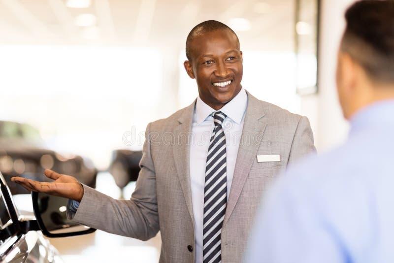 African salesman presenting car. Handsome african salesman presenting new car to clients stock photography