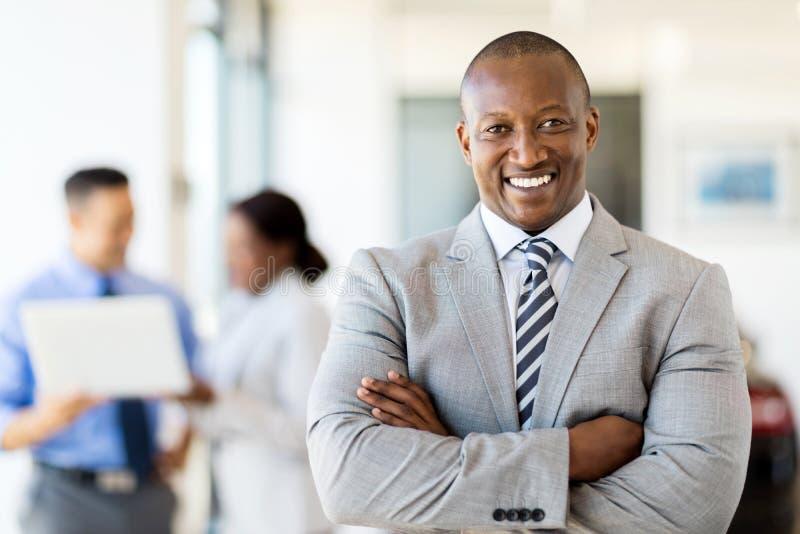 African salesman standing dealership. Happy african salesman standing at car dealership with colleagues on background stock photo