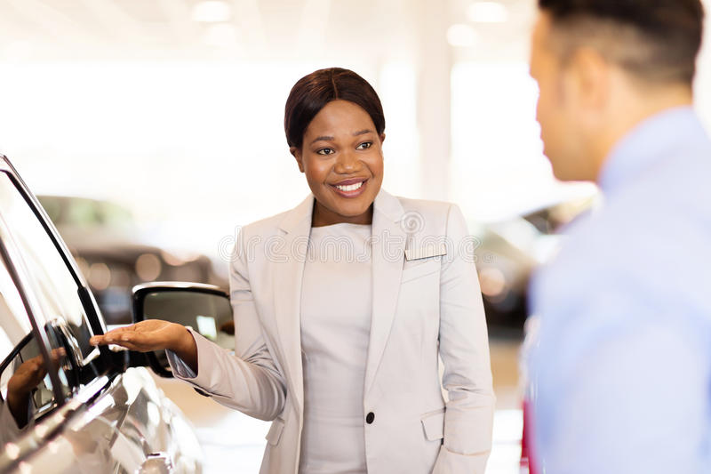 African saleswoman selling car. Professional african saleswoman selling car to a customer in showroom royalty free stock photos