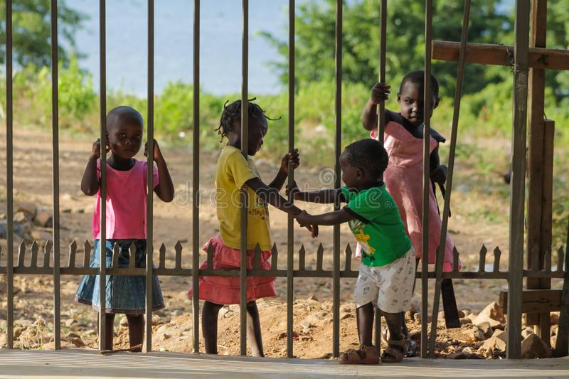 African poor children near fence. African small poor children boys and girls on the street. Slum african people village life stock image