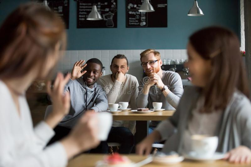 African smiling man waving hand greeting girls meeting in cafe stock photo
