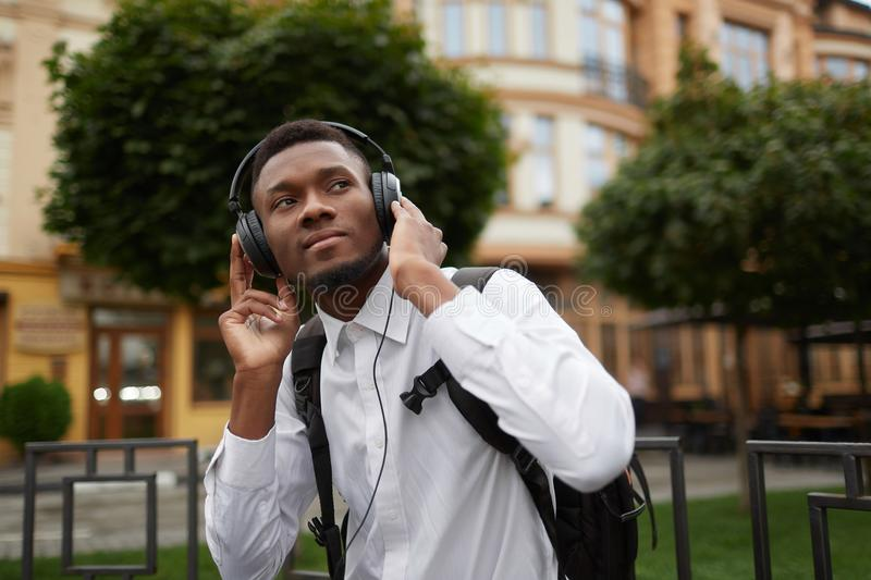 African student at break listening music at park. stock photos