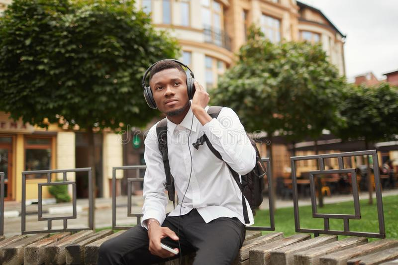 African student at break listening music at park. stock photography