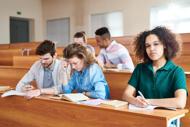 African student studying in university. Content confident African-American student girl with curly hair sitting at university desk and making notes in workbook royalty free stock photo