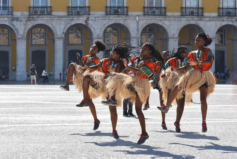 An African style dance group performing in Lisbon in Commerce Square. A group of six young Afro Caribbean women practising African style synchronised dancing in stock photography