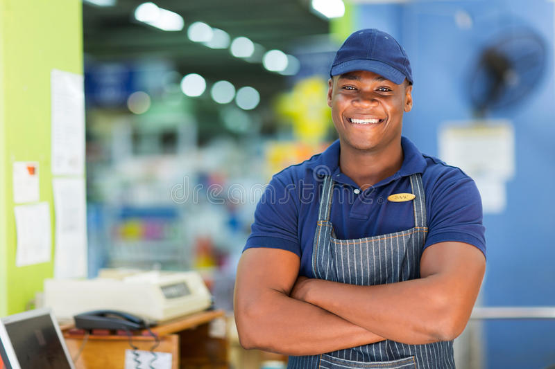 African supermarket cashier. Handsome african supermarket cashier standing at checkout royalty free stock images