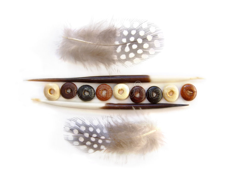 African theme decor elements. White, brown and black beads between two porcupine quills and guinifowl feathers stock photography