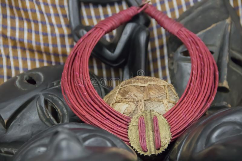 African tribal necklace with background made of African artifacts royalty free stock image
