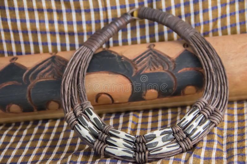 African tribal necklace with background made of African artifacts stock photography