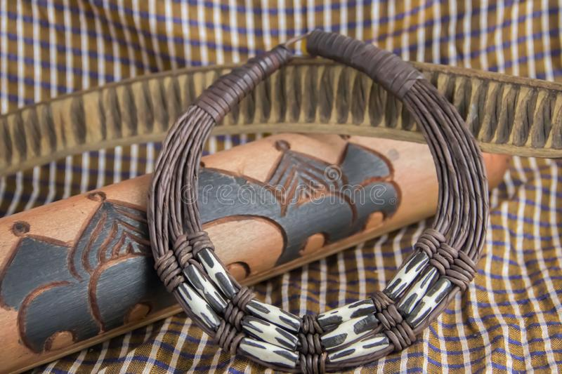 African tribal necklace with background made of African artifacts stock photo