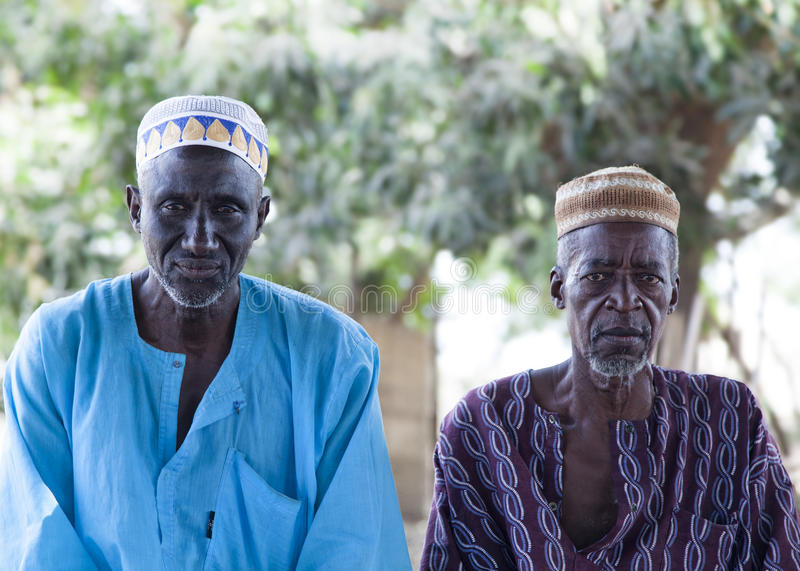 African village elders in traditional colorful clothes and muslim caps royalty free stock photo