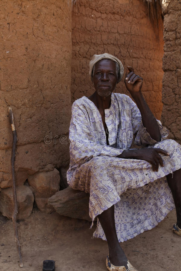African village headman resting in the shade of his hut royalty free stock photo