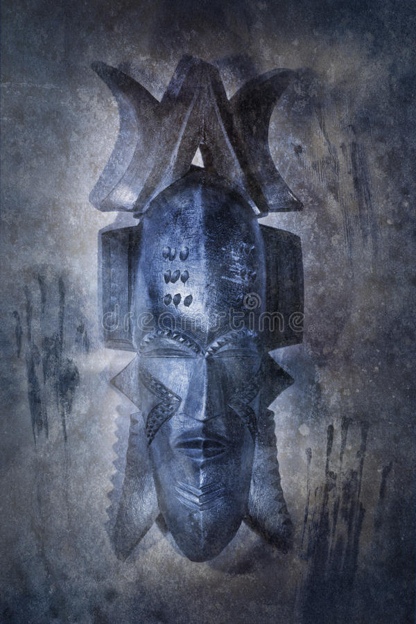African Voodoo Mask. Against a grunge textured background of primitive, ghostly cave painting hand prints stock image