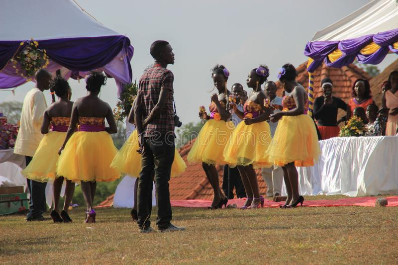 African wedding party in the park with beautiful girls dancing in traditional dresses with yellow skirts and the leading of the ce. Kampala, Uganda - January 24 stock photo