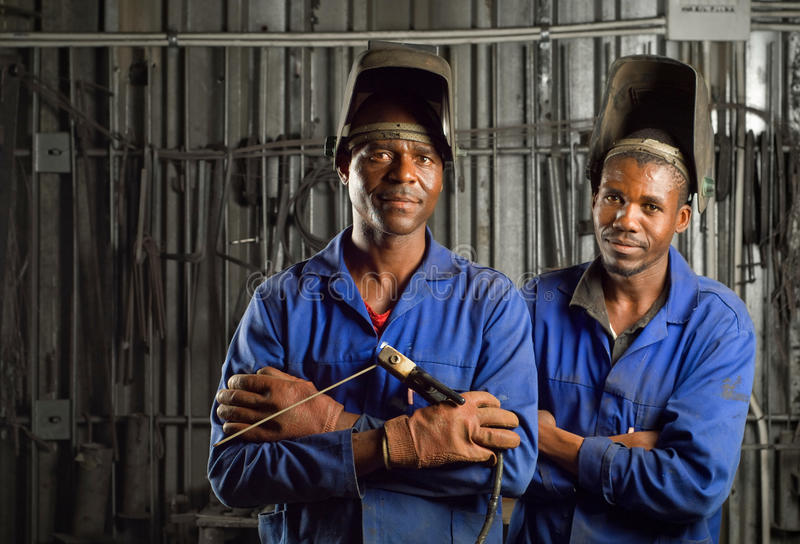 African welder with mask. South African or American black workers or welders in factory royalty free stock image